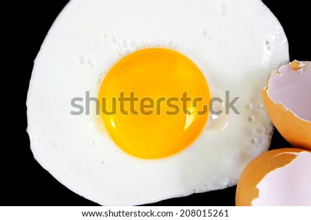 Fried egg isolated on a black background and shells - stock photo