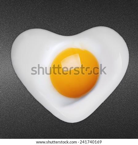 Fried egg like heart on frying pan  - stock photo