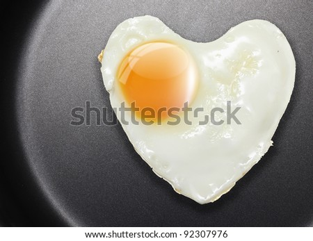 Fried egg like heart on frying pan with place for your text.
