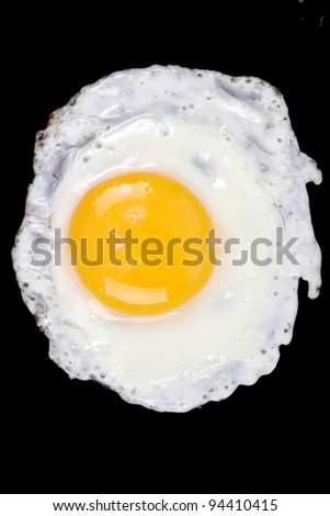 Fried egg on a black frying pan isolated, close-up shot