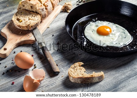 Fried egg on a pan and served with bread - stock photo