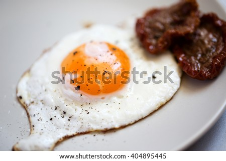 Fried egg on a plate with peppers