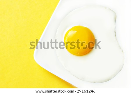 Fried egg on a white plate with a yellow background.