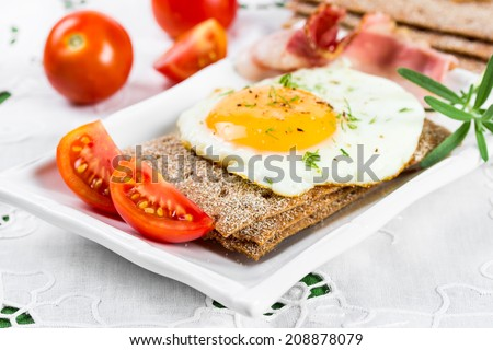 Fried egg on crisp bread and tomatoes.