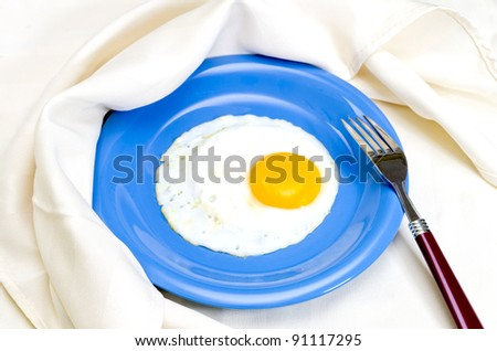 Fried egg on plate with fork and napkin. - stock photo