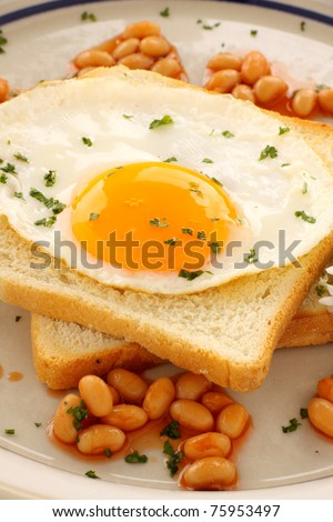 Fried egg on toast parsley garnish and baked beans. - stock photo