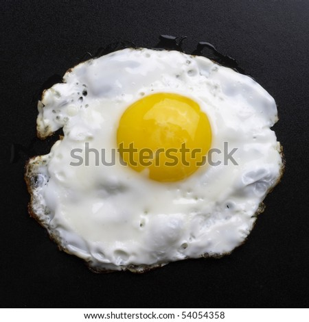 Fried egg over black textured plate background - stock photo
