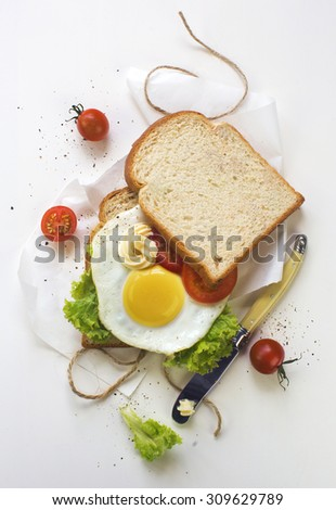 Fried egg sandwich and espresso on white dinning table top. Close-up overhead view. - stock photo