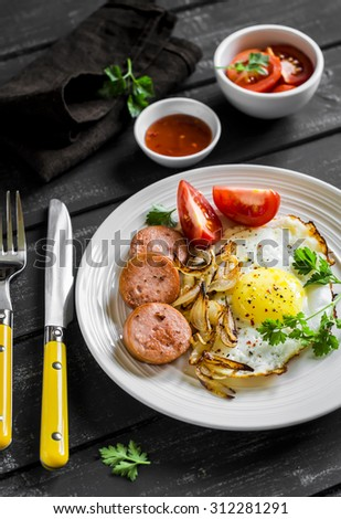 fried egg, sausage, tomatoes - tasty Breakfast or snack, on the bright plate on a dark wooden background