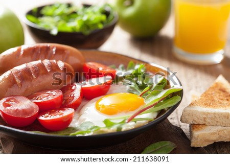 fried egg sausages tomatoes for healthy breakfast  - stock photo