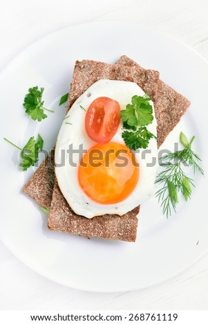 Fried egg, tomato slice and parsley on crispbread, top view - stock photo