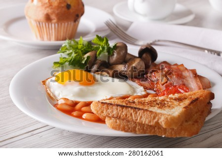 Fried egg with bacon and beans on a plate close-up. horizontal  - stock photo