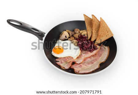 Fried egg with bacon in a frying pan - stock photo