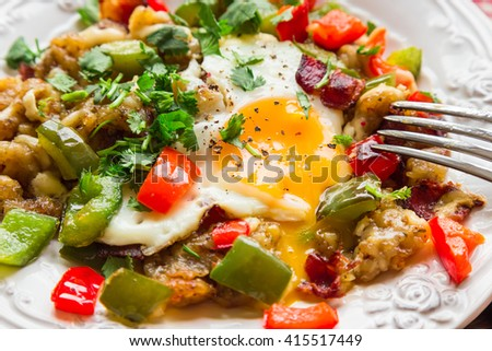 Fried egg with pepper, bacon, potatoes and cilantro. Selective focus. - stock photo