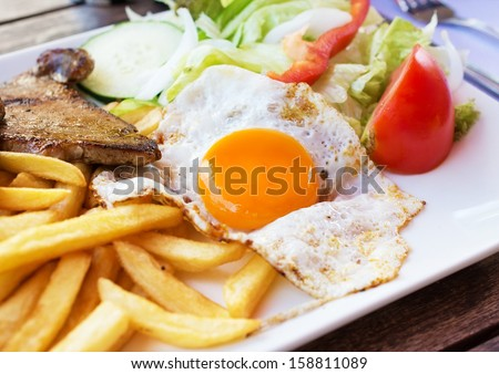 Fried egg with potato fries, grilled steak and vegetables. - stock photo