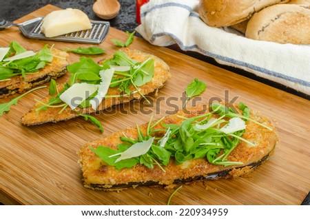 Fried eggplant, fried in parmesan crust, arugula salad with shavings of Parmesan cheese, fresh bread - czech dalam���¡nek - stock photo