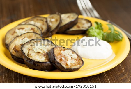 Fried eggplant with garlic and sour cream on a yellow plate.  - stock photo