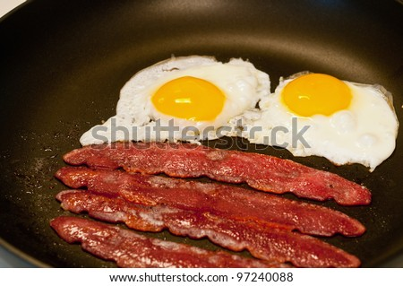 Fried eggs and bacon cooking in a skillet - stock photo