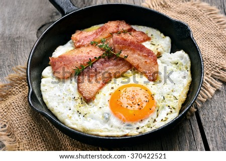 Fried eggs and bacon in frying pan, close up view - stock photo