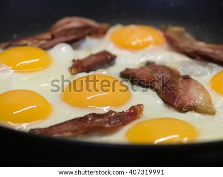 Fried eggs and pork bacon rashers in pan - stock photo