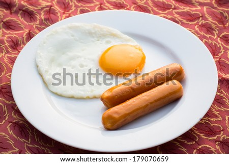 Fried eggs and sausage on a white porcelain plate