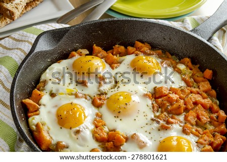 Fried eggs and sweet potato hash in cast iron skillet sitting on green striped kitchen towel with whole grain toast and stacked plates - stock photo
