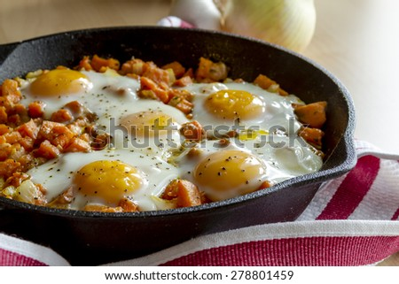Fried eggs and sweet potato hash in cast iron skillet sitting on red striped kitchen towel - stock photo