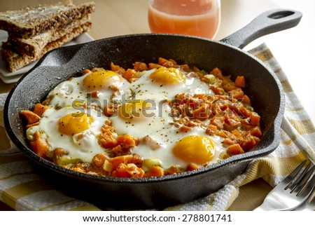 Fried eggs and sweet potato hash in cast iron skillet sitting on yellow striped kitchen towel with whole grain toast and grapefruit juice - stock photo