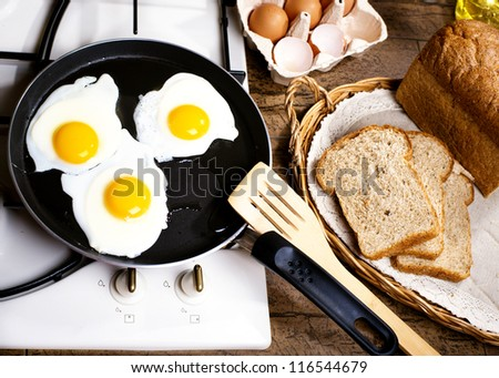 Fried eggs in a frying pan on a gas cooker - stock photo