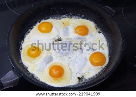 Fried eggs in a frying pan on the stove - stock photo