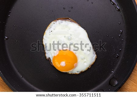 Fried eggs in a frying pan, view from above - stock photo