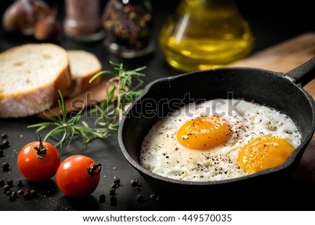 Fried eggs in a frying pan with cherry tomatoes and bread for breakfast on a black background. - stock photo