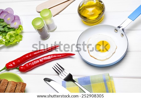 Fried eggs in a frying pan with fennel, tablewares, orange juice in a glass and chilli.  - stock photo