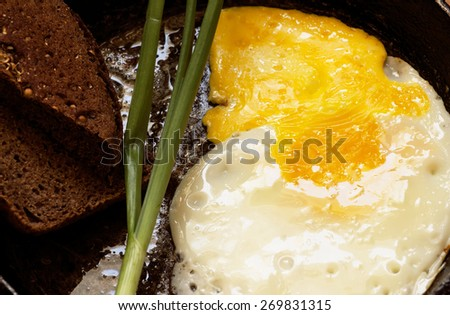 fried eggs in a frying pan with rye bread - stock photo