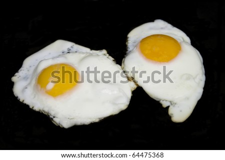 Fried eggs in isolated over black