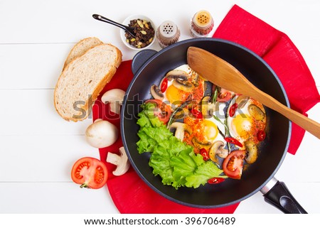 Fried eggs in pan with tomato, bread, pepper and mushrooms on wooden background - stock photo