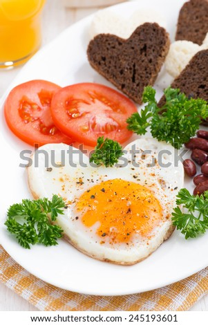 fried eggs in the form of heart for breakfast Valentine's Day, close-up, vertical - stock photo