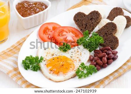 fried eggs in the form of heart for breakfast Valentine's Day on plate, close-up - stock photo