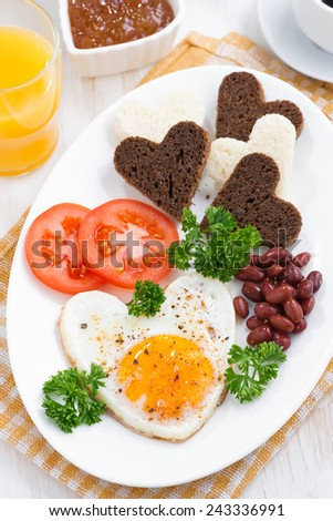 fried eggs in the form of heart for breakfast Valentine's Day, vertical, top view - stock photo