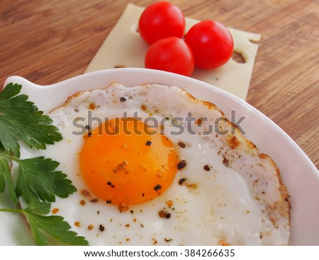 Fried Eggs on a plate (wooden background) - stock photo