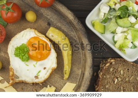 Fried Eggs on a wooden background. Fried eggs and vegetables on the cutting board. Homework healthy food. - stock photo