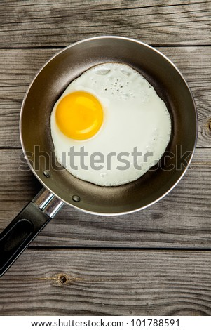 Fried eggs on a wooden table, breakfast - stock photo
