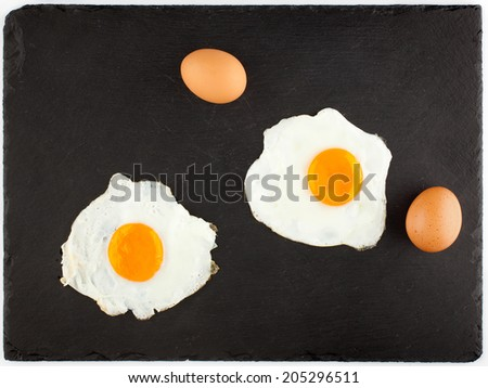 Fried eggs on black plate - stock photo