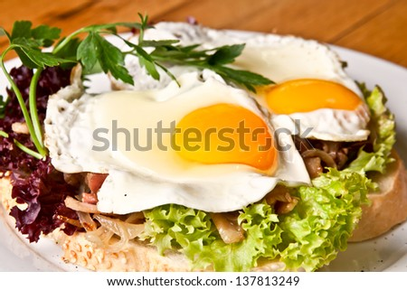 Fried eggs on fresh bread - stock photo