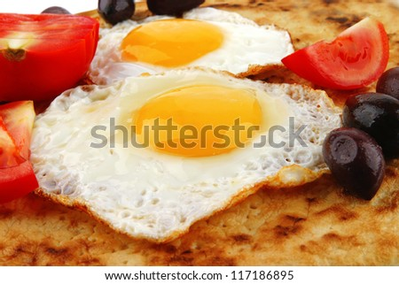 fried eggs on pancake over white with vegetables - stock photo