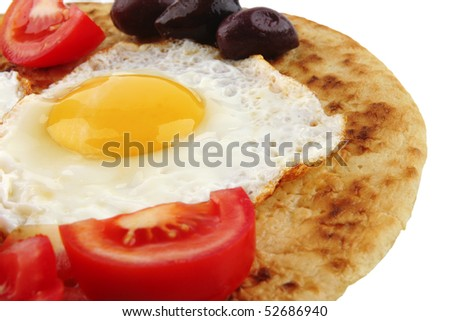 fried eggs on pancake over white with vegetables