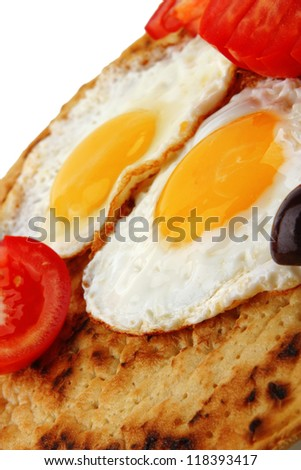 fried eggs on pancake with tomato and olives