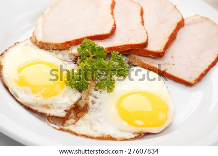 Fried eggs with bacon and parsley, close-up