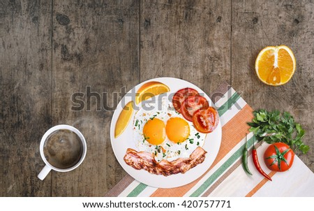 Fried eggs with bacon breakfast. Toast, coffee tomato and chili on aged dark wooden table. Top view with copy space - stock photo
