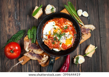 fried eggs with bacon in a pan close-up on wood background. - stock photo